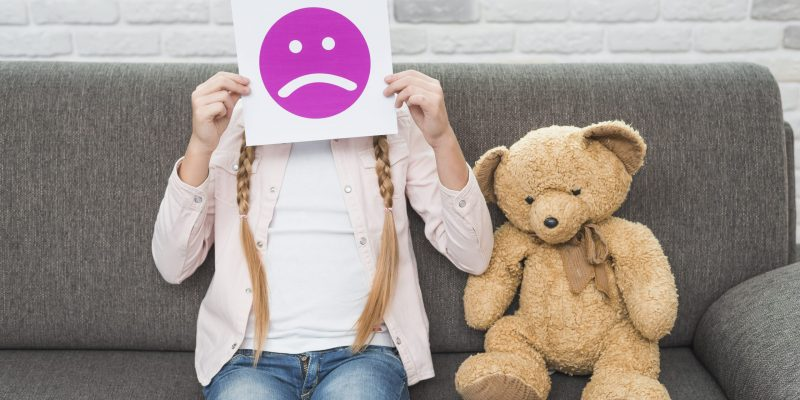 close-up-of-girl-sitting-with-teddybear-holding-sad-face-emoticons-paper-in-front-of-her-face