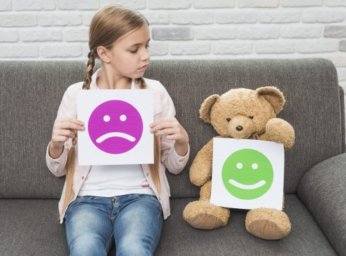 girl-holding-sad-smileys-paper-looking-at-teddy-bear-with-happy-smileys