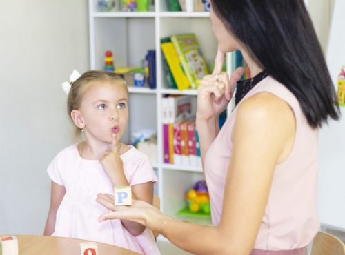 Speech therapist teaches the girl to say the letter